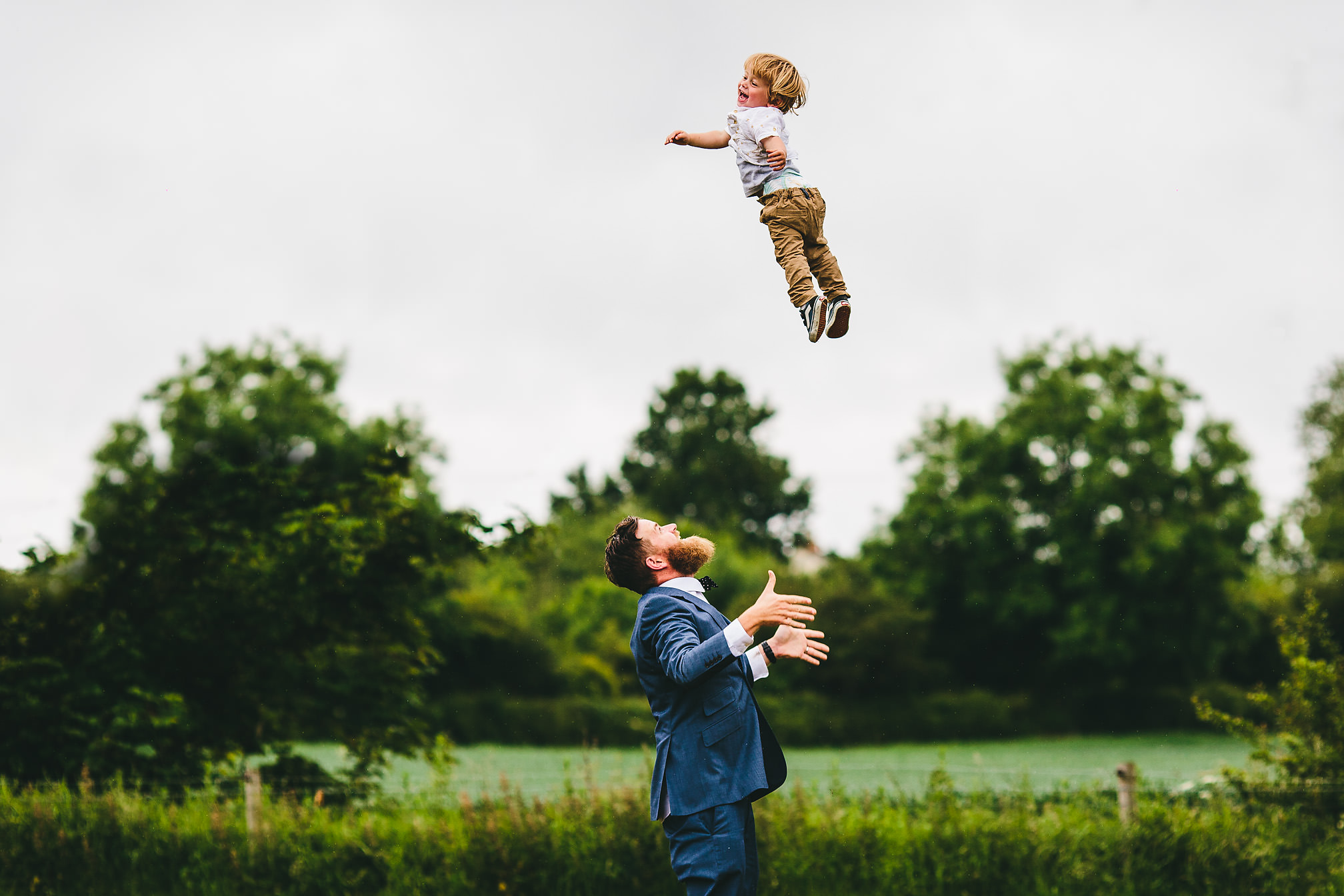 Groom throwing his son in the air with joy