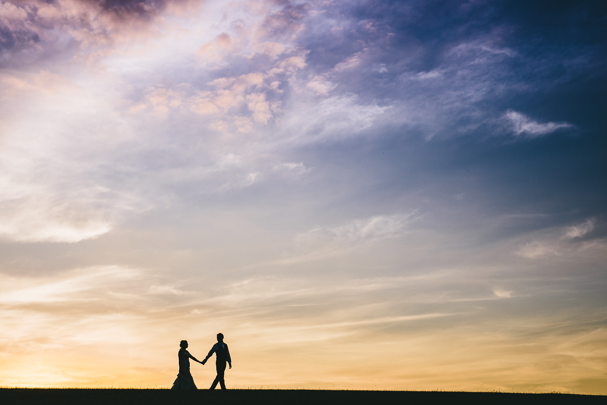 Wedding couple walking during sunset