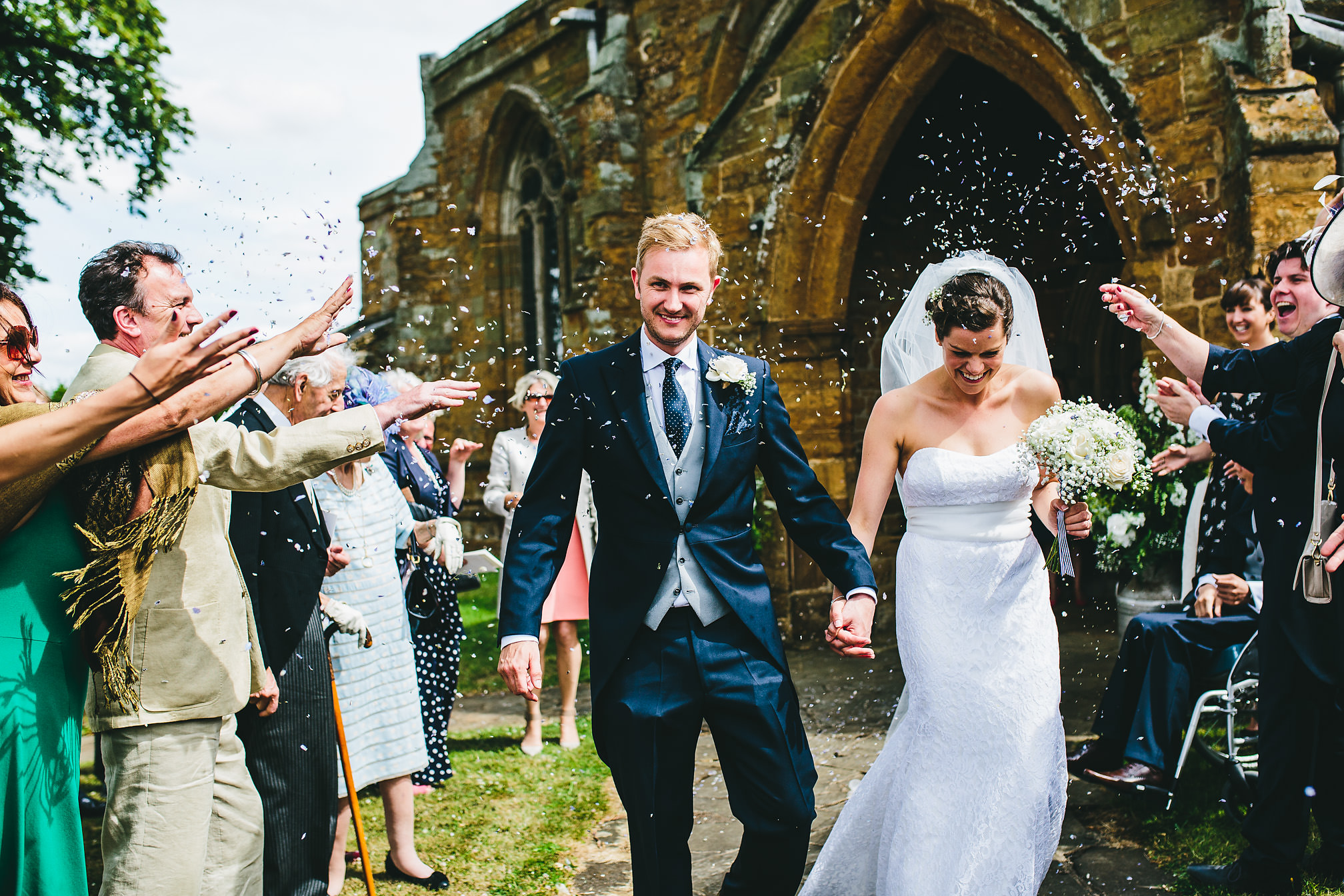 Couple running out of church to a confetti shower
