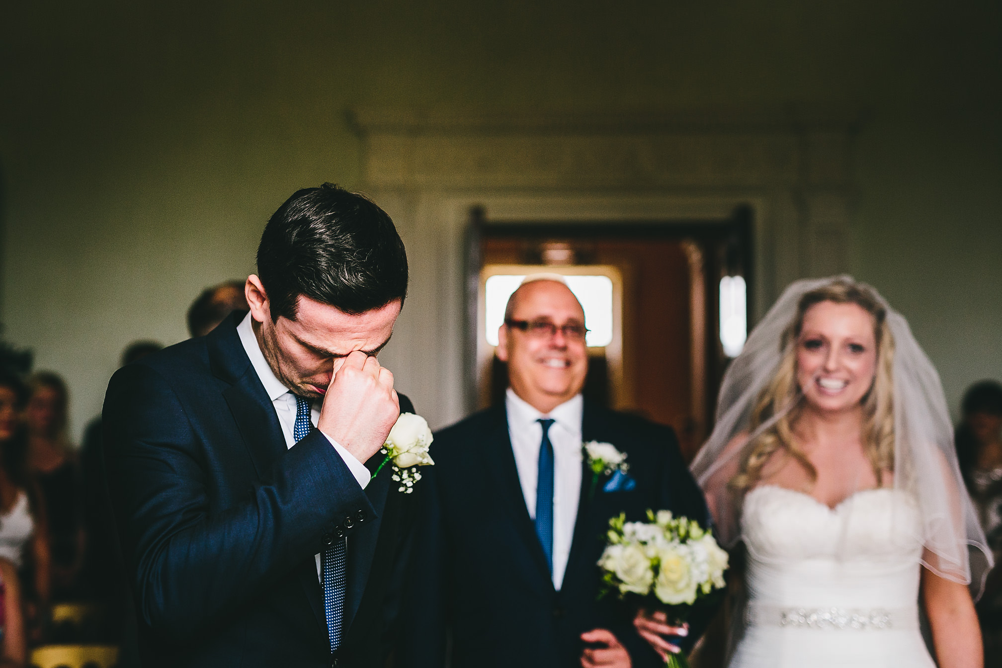 Groom crying as his bride walks down the isle