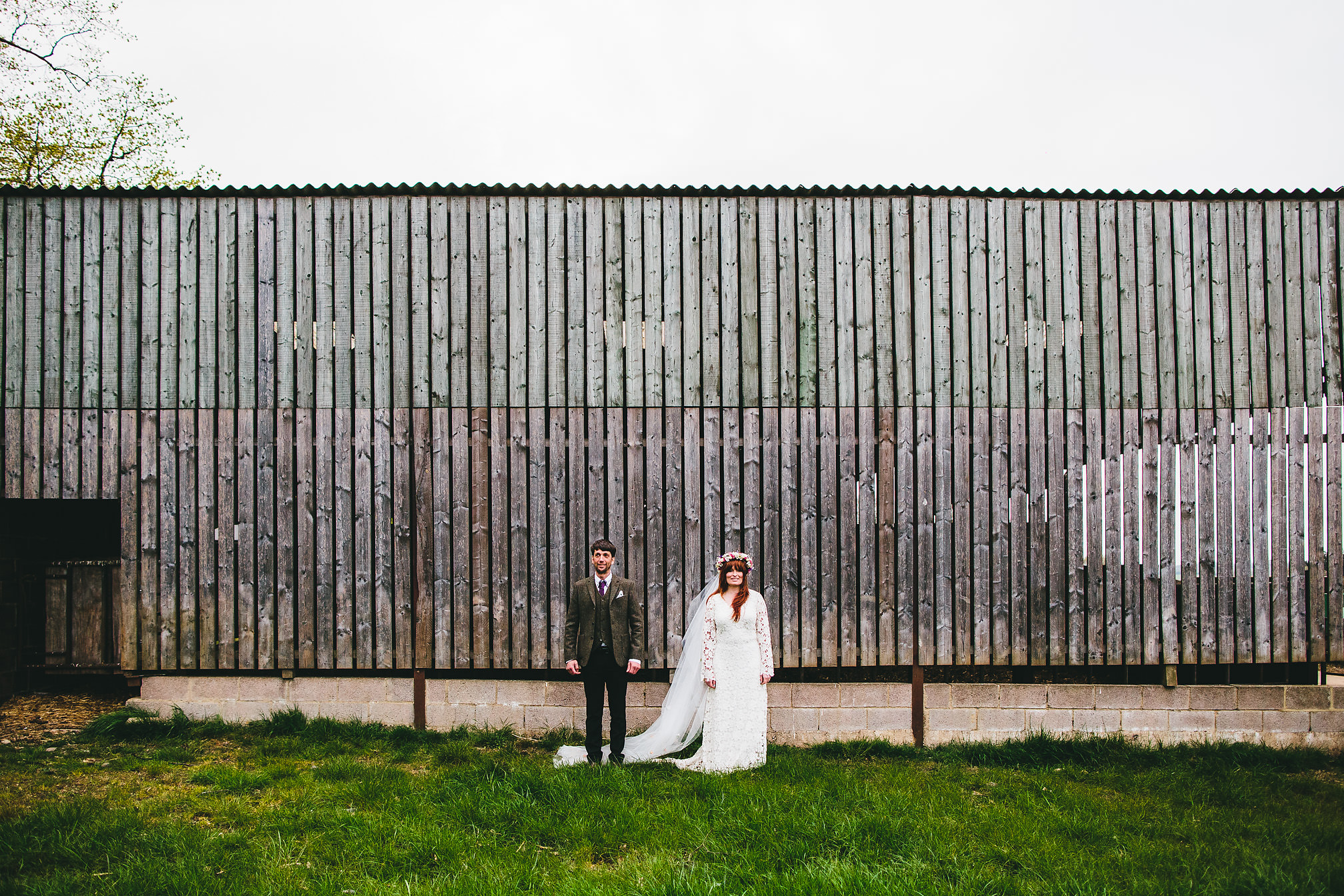 Couple posing next to a barn