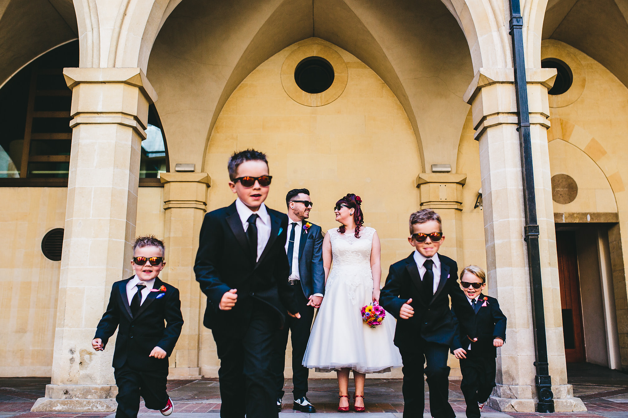 Young wedding guests running towards the camera