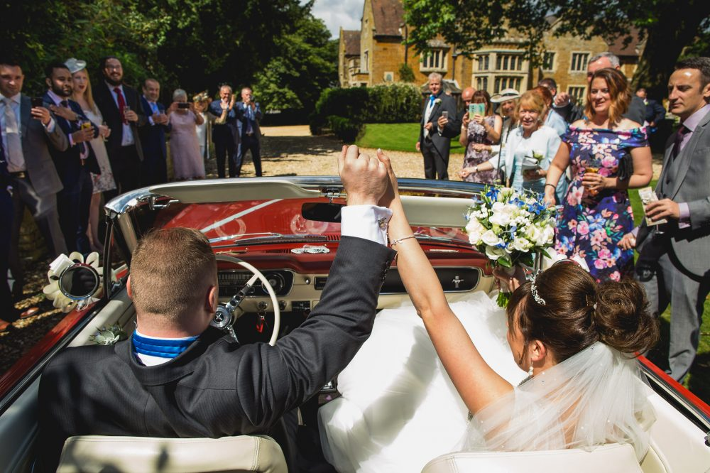 Bride and Groom fist pump as they arrive back at Highgate House, Northants
