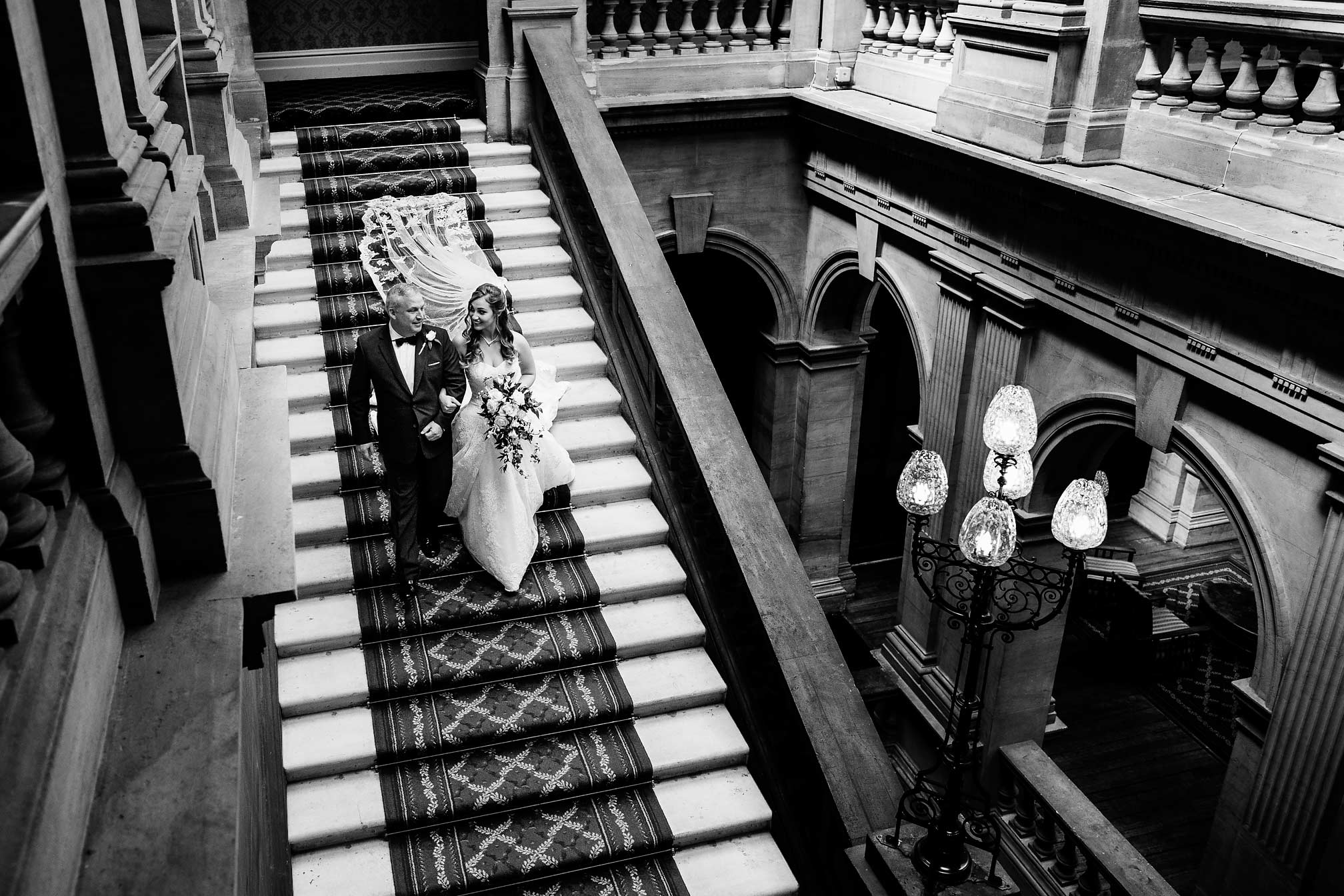 Bride walking down the grand stairs at Heythrop Park