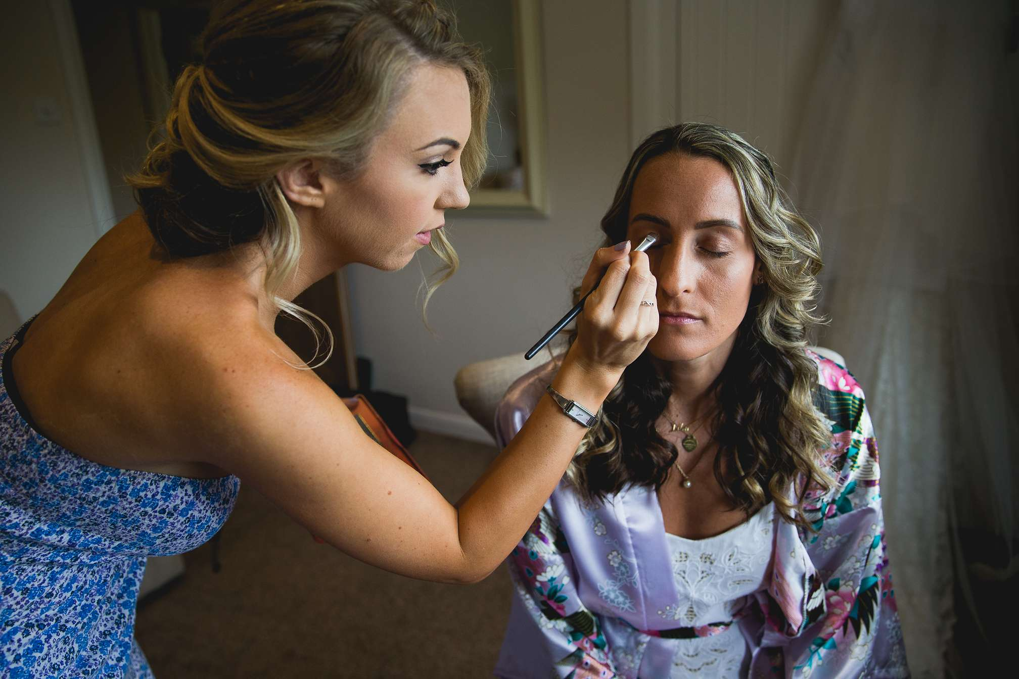 The bridesmaids helping each other out with makeup