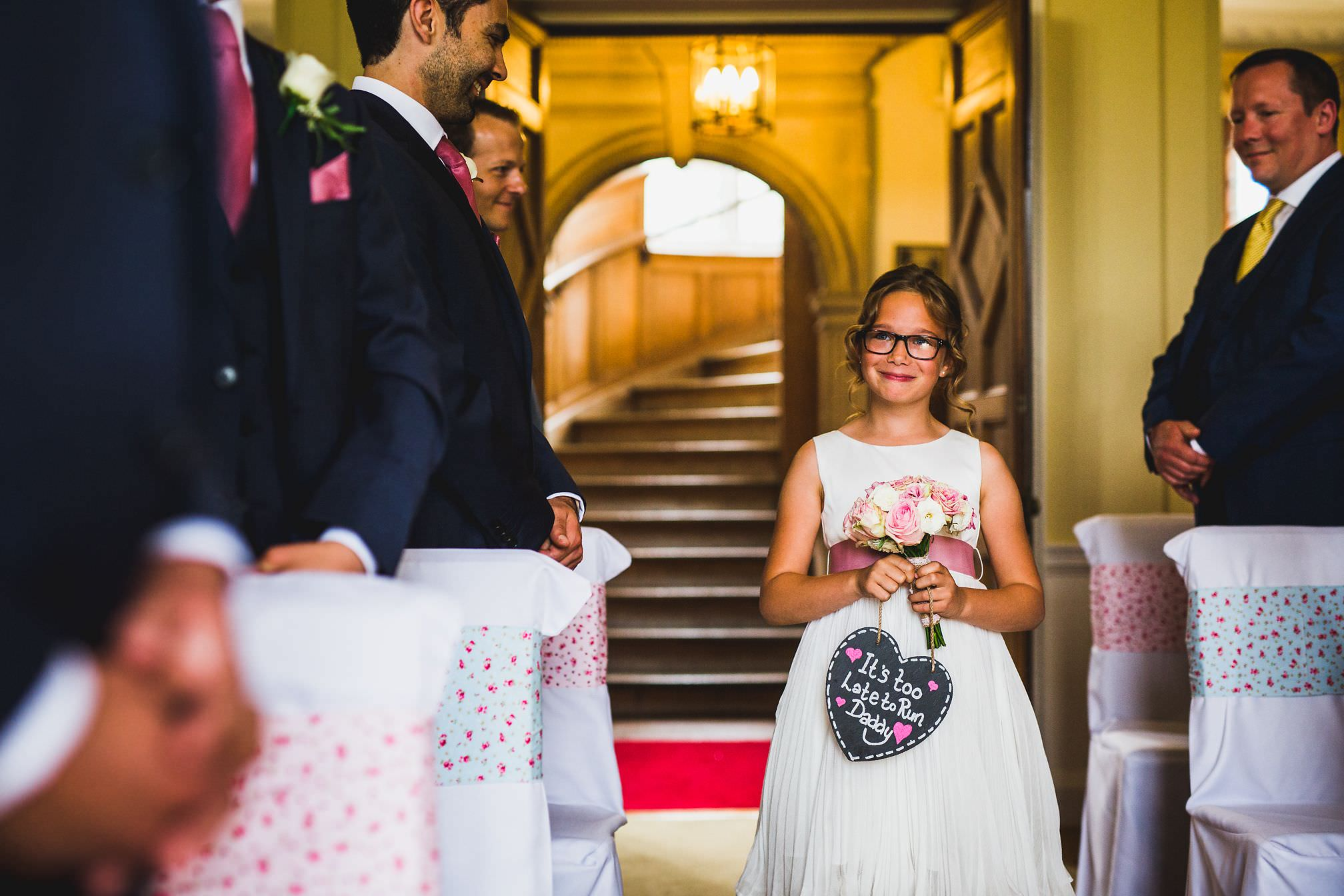 MyWed Editors Choice - Flower girl walking down the isle with a sign