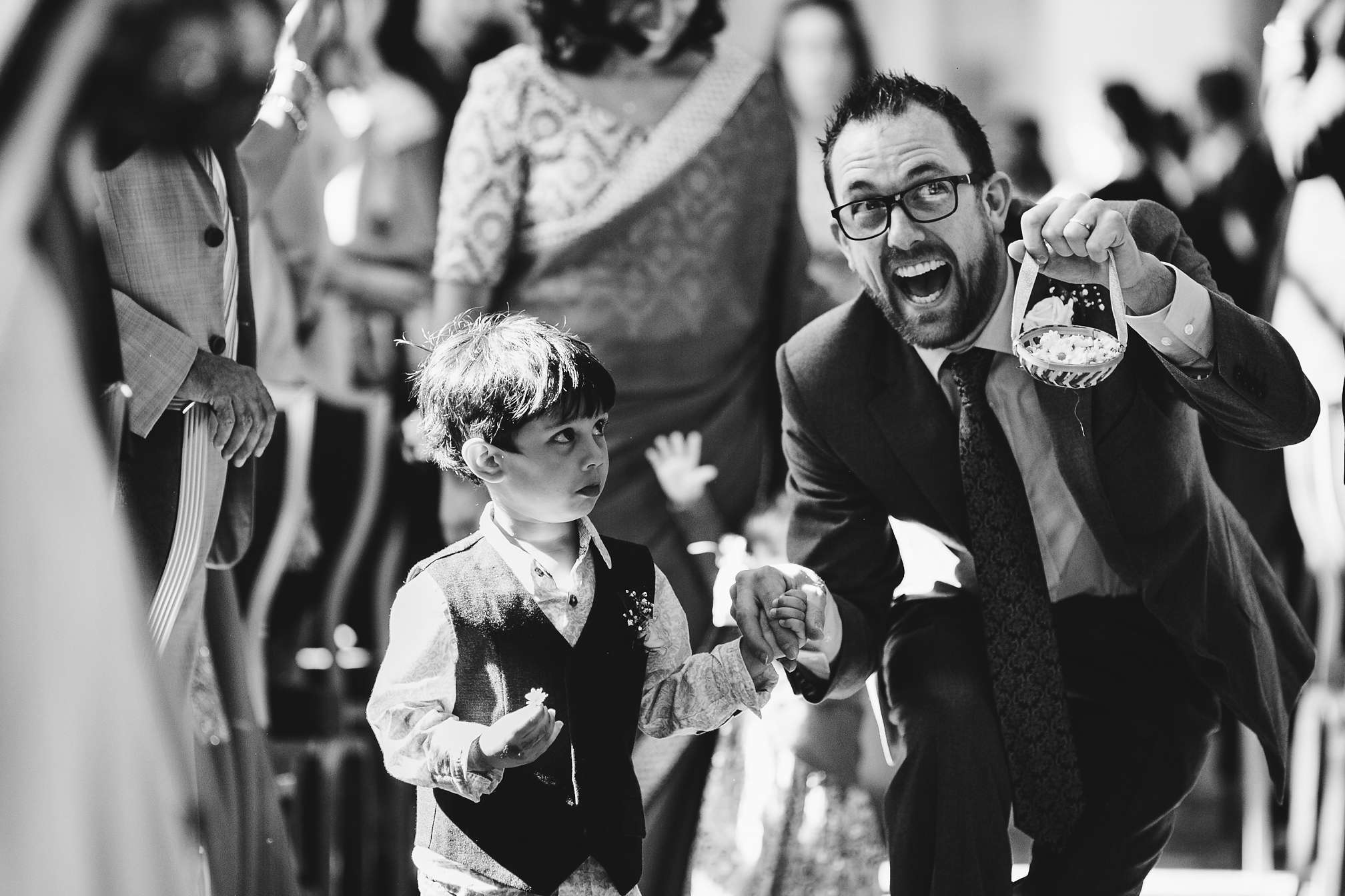Funny black and white photo of a page boy and his dad walking down the isle