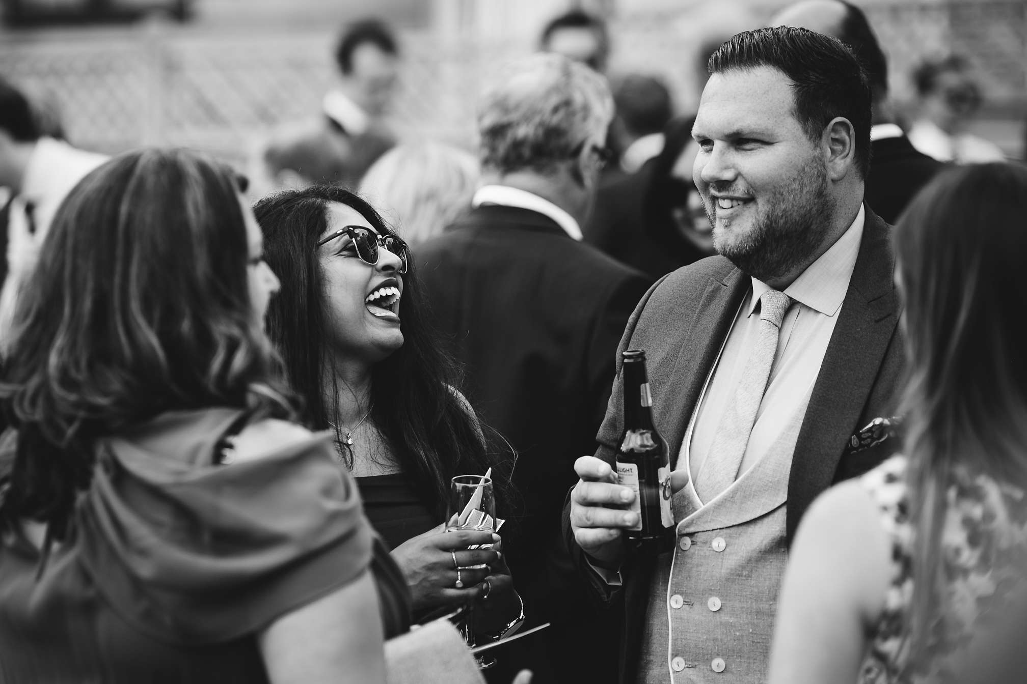 Black and white picture of wedding guests chatting and laughing