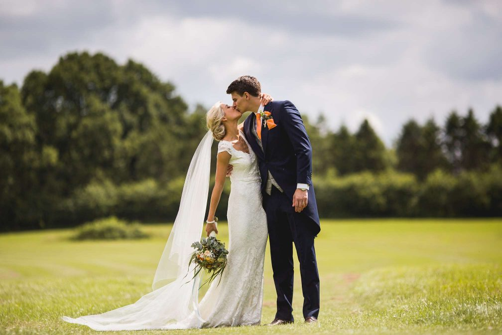 Jane and Jon kissing on the golf course at Brookfield Barn
