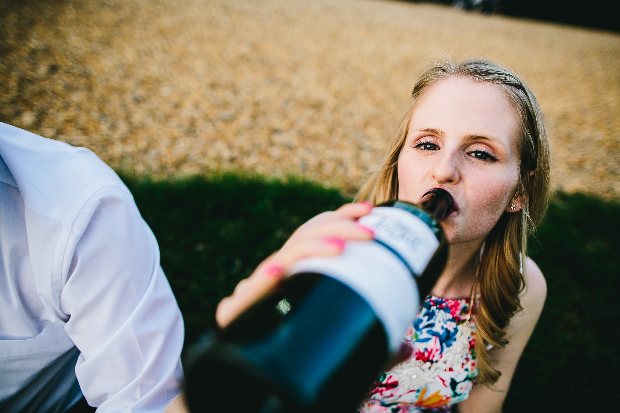 Wedding guest drinking red wine from a bottle