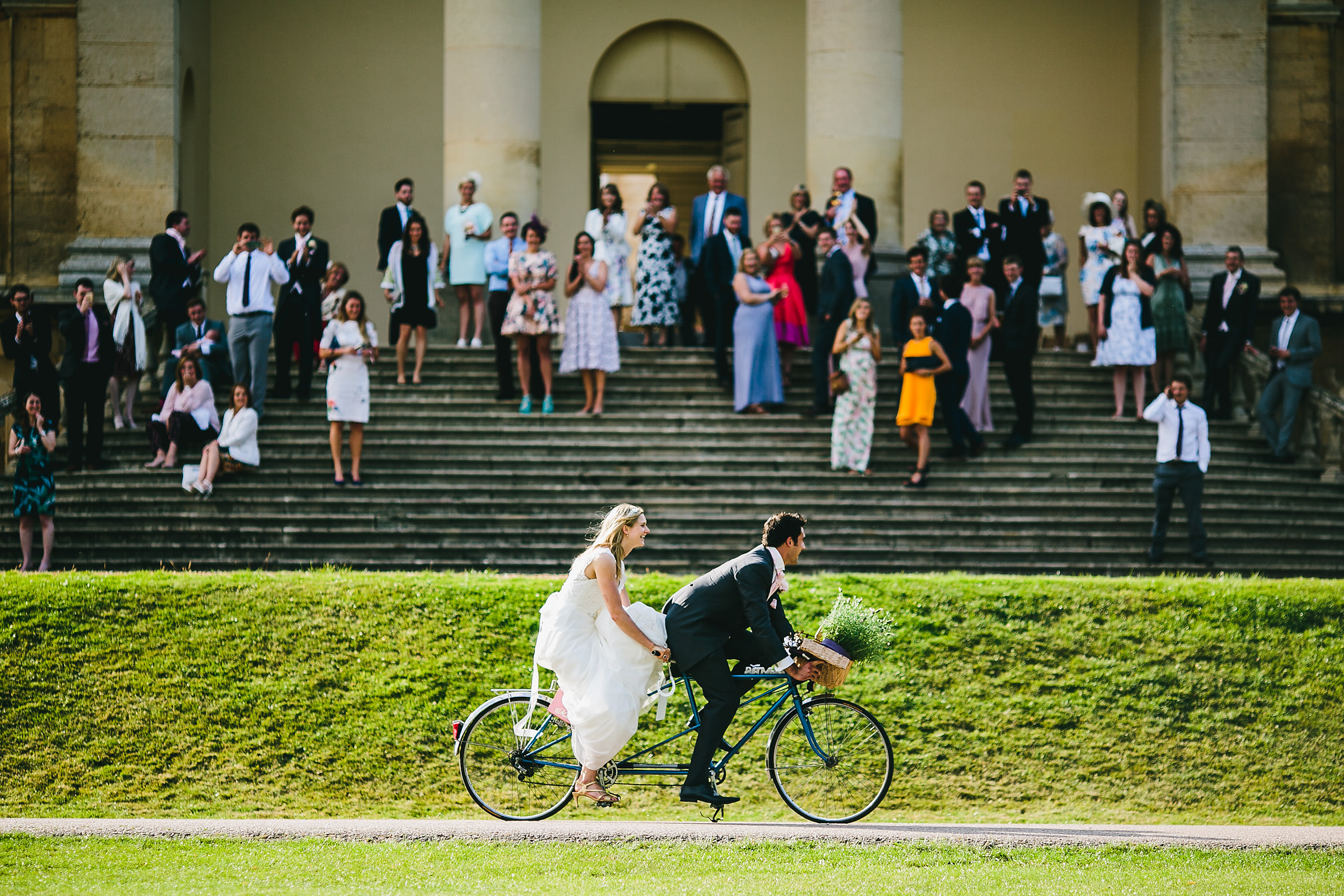 Bride and Groom cycling away on a tandem
