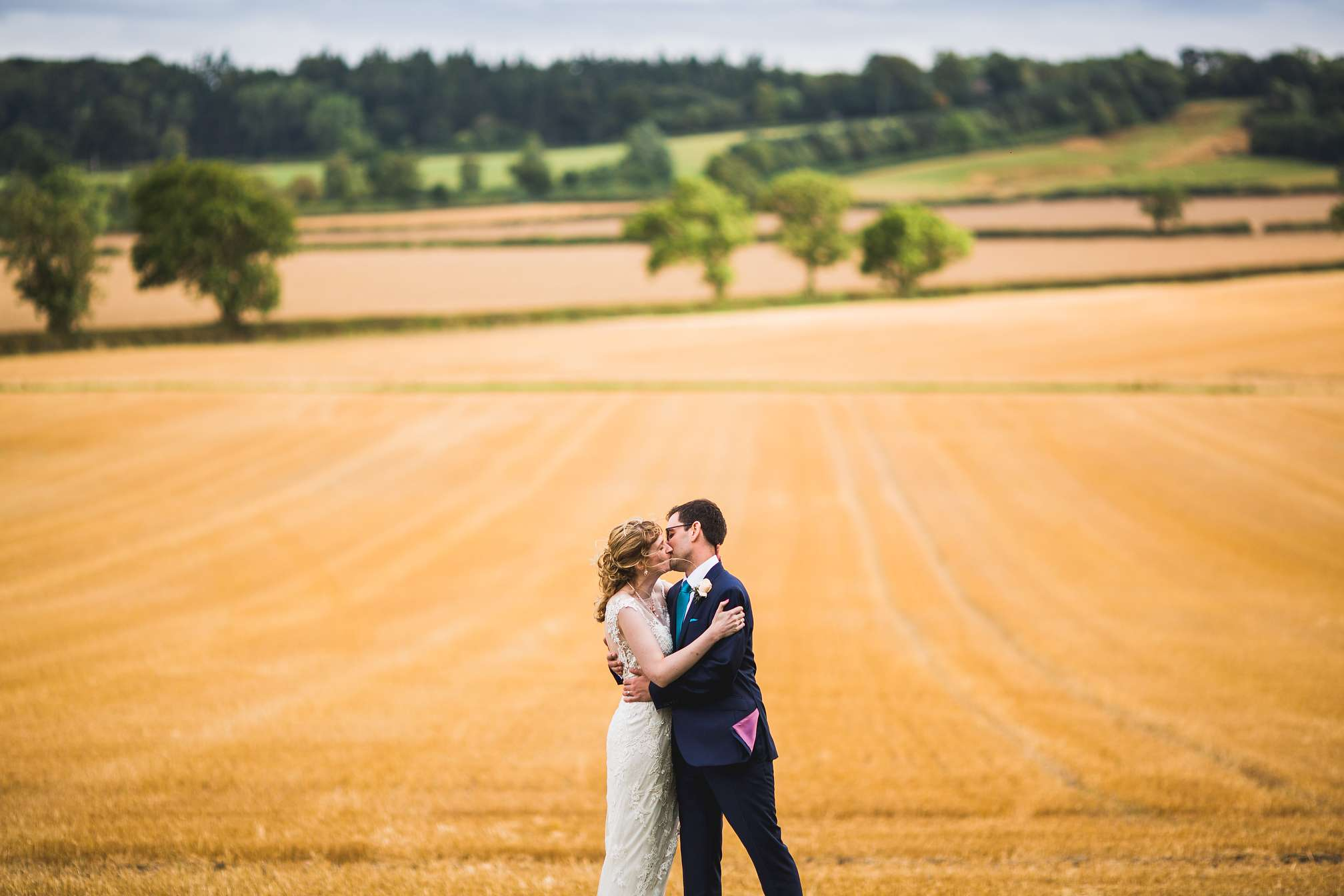 Couple kissing in the field at Hothorpe Hall in Northamptonshire