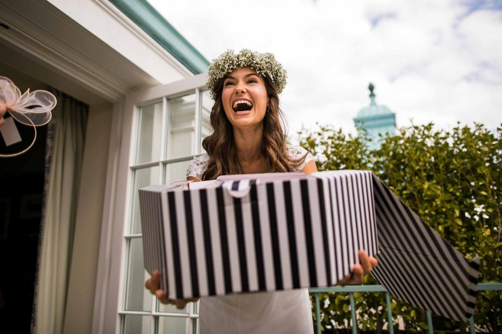Pretty laughing bride with a hat box