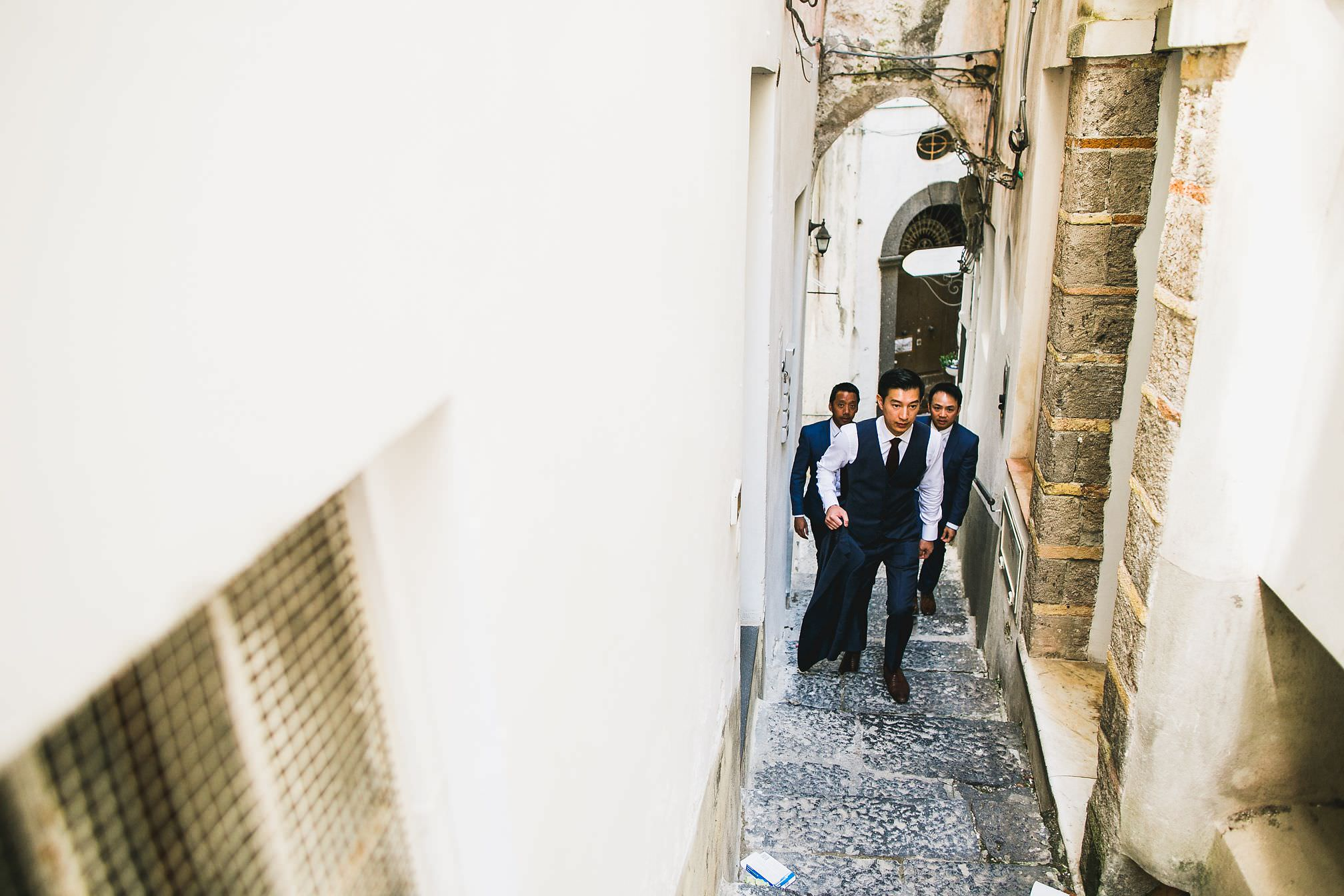Groomsmen walking up a narrow Amalfi street
