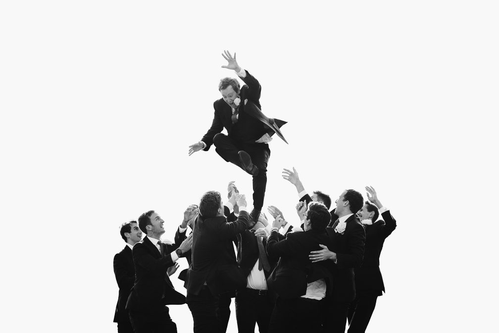 Sam being thrown in the air by his groomsmen