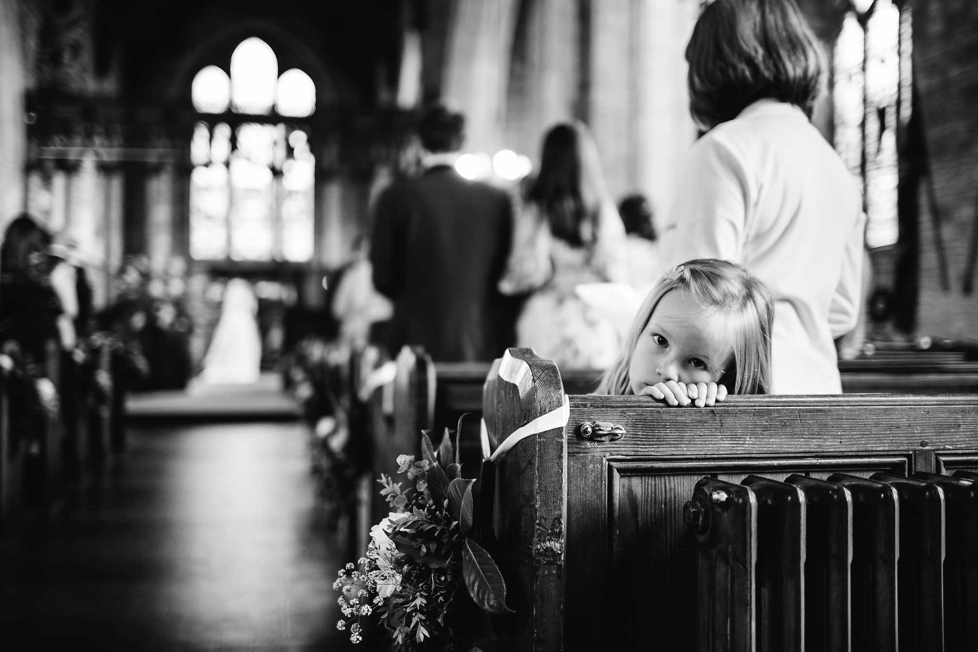Cute young girl sat at the back of the church during a wedding ceremony